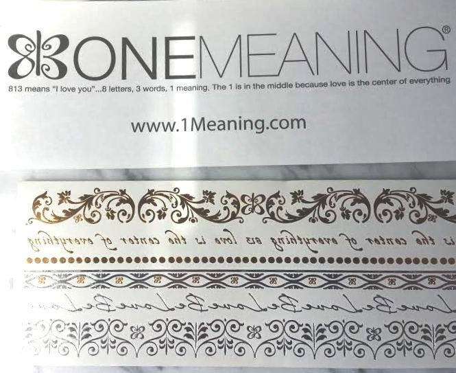 "One Meaning Love Light Tattoo'OMs  Let your love light shine with our meaningful flash. Beautiful and ethereal temporary metallic tattoos to grace your body however you'd like, wherever you'd like (avoid eye areas please). After three years of research we finally get to bring these beautiful adornments to you!    Each package contains 2 sheets (3""x8"" each) of meaningful gold and silver metallic tattoos: Bands and Medallions. Bands are lacy patterns and words (""Love is the Center of Everything"" and ""Be Love"") great for bracelets, anklets, armbands, or a love line down your back. Medallions are a collection of some of our most popular designs with tiny One Meaning ""I Love You"" Butterflies throughout. So pretty! Share your photos with us so we can be inspired by you.   Wear Something with Meaning.®     Lasts 4-6 days with gentle care. Apply with water (directions included) remove with baby oil. For adult use. Do not apply near eyes, on sensitive or broken skin, or if you have allergies to any adhesive materials."