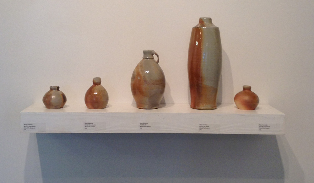 "Woodfired vessels by Mary Sweeney (bottom,) Soda fired cups by Tyler Gulden (top,) Woodfired  vessels by Mary Sweeney, Woodcut prints by Jake Cassevoy, 1900s Copper Clock Tower Numerals, 18"" (right)"