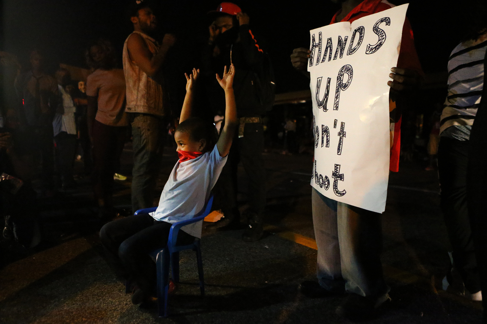 "Donovan Hope, 5, holds his hands up as protesters on West Florissant Avenue shout ""hands up, don't shoot"" on Thursday, Aug. 14, 2014, in protest of the shooting death of 18-year-old Michael Brown by Ferguson police officer Darren Wilson on Aug. 9."