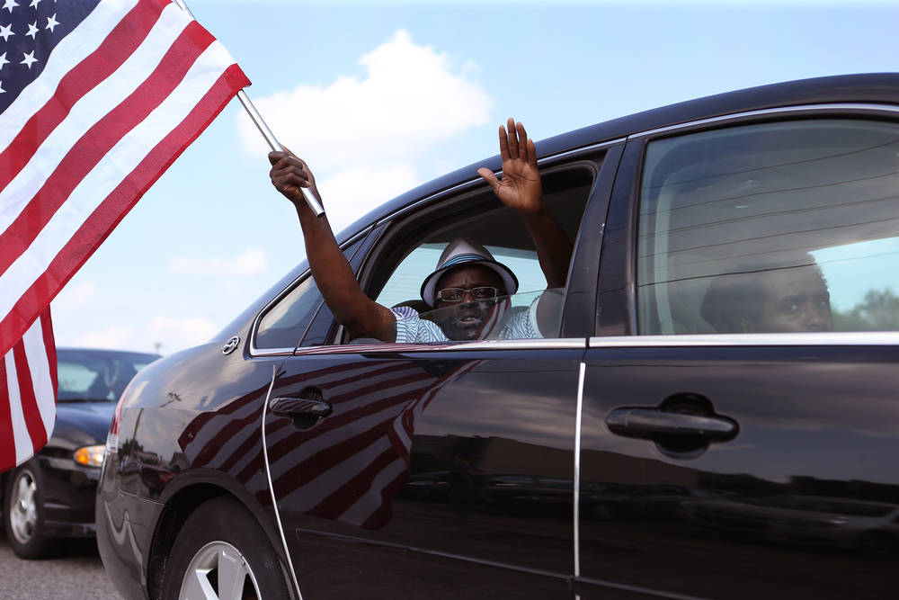 "Supporters drive by honking their horns and shouting ""hands up, don't shoot"" on West Florissant Avenue in Ferguson on Monday, Aug. 18, 2014 as part of ongoing protests in the shooting death of 18-year-old Michael Brown by Ferguson police officer Darren Wilson."
