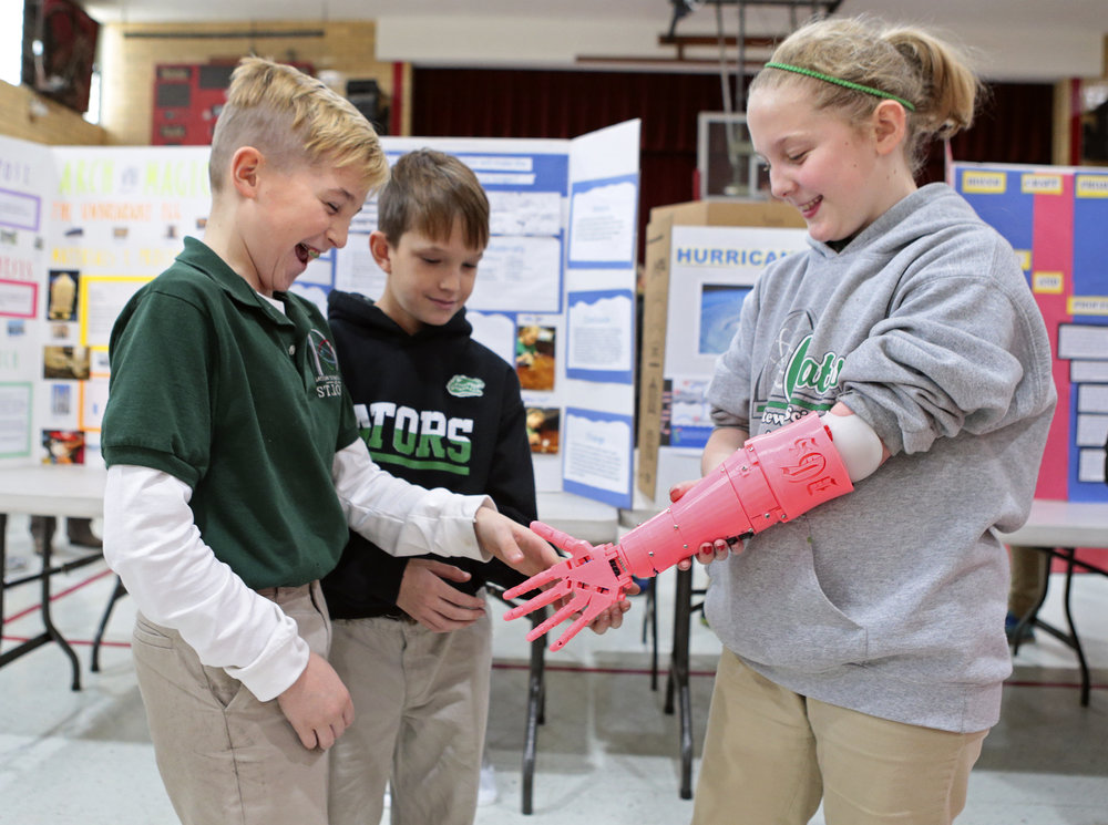 Delanie Gallagher (right), 10, of Spanish Lake, shakes hands with classmate Michael Gallaway, 11, of St. Louis, using her new robotic prosthesis at Gateway Science Academy of St. Louis on Wednesday, Dec. 14, 2016, in St. Louis. Also pictured is Dylan Day, 11, of St. Louis.