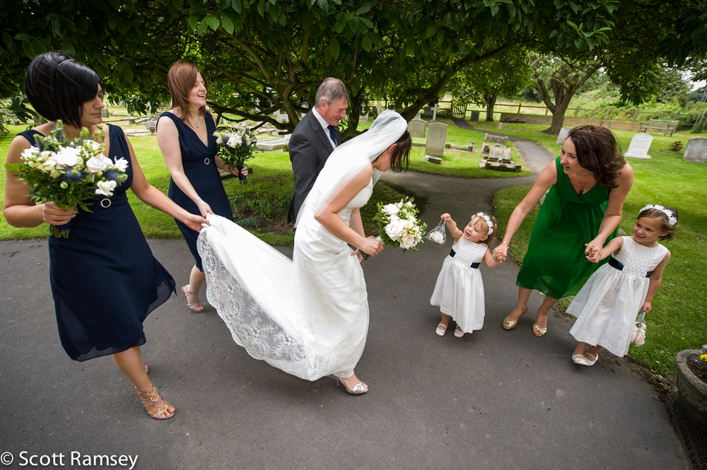 A bride is handed a gift from her flower girl as she arrives for her church wedding in Farnham, Surrey.