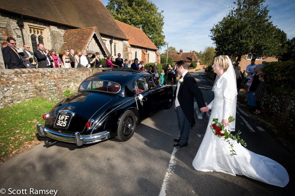 The groom leads his bride to a classic car as they leave after getting married at St Thomas Church in East Clandon, Surrey.