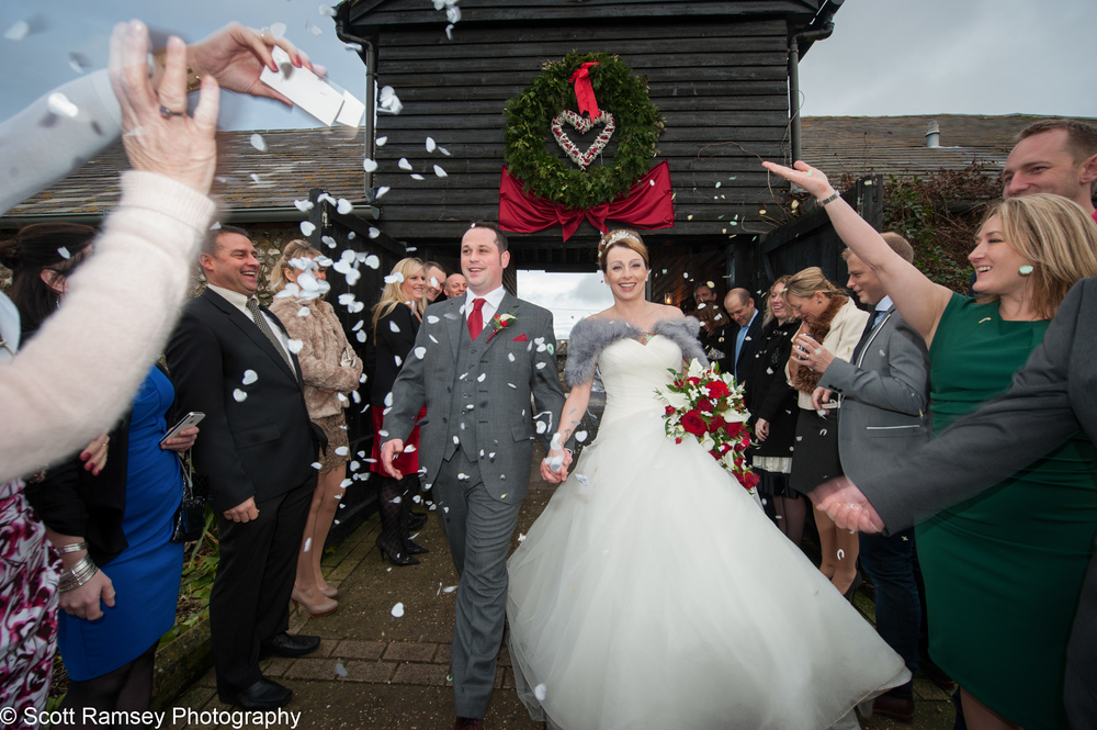 Upwaltham Barn Wedding - Jo and Neil are covered in confetti as they celebrate their wedding at Upwaltham Barns in West Sussex.