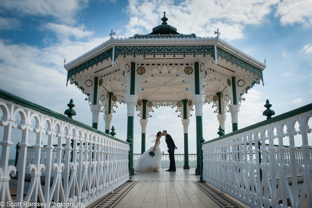 Brighton Wedding Photography. A couple kiss silhouetted against a blue sky whilst standing in the Bandstand on Brighton Seafront in East Sussex.