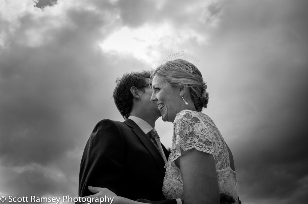 Blackstock Farm Barn Wedding. A Groom whispers into the ear of his bride during their wedding at Blackstock Barn in East Sussex.