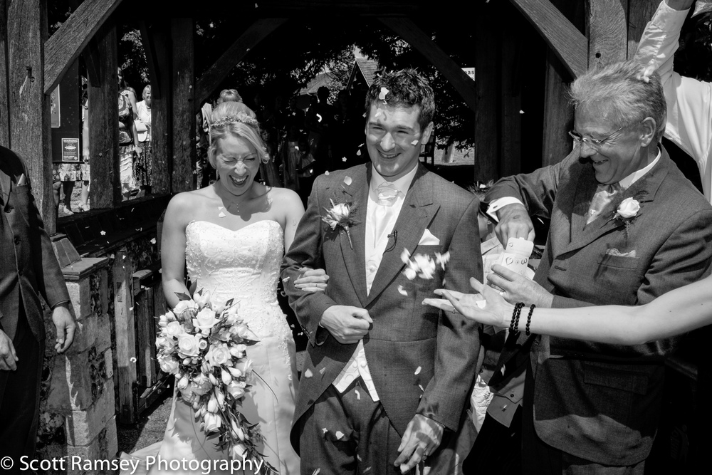 Rustington Wedding Photography. Jamie and Geoff are covered in confetti after getting married at St Peters and St Pauls church in Rustington, West Sussex, UK.