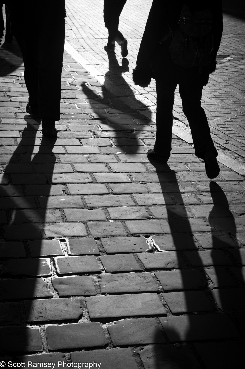 In the winter sun shoppers looking for a Boxing Day sale bargain cast shadows onto the street in Chichester, West Sussex, UK.