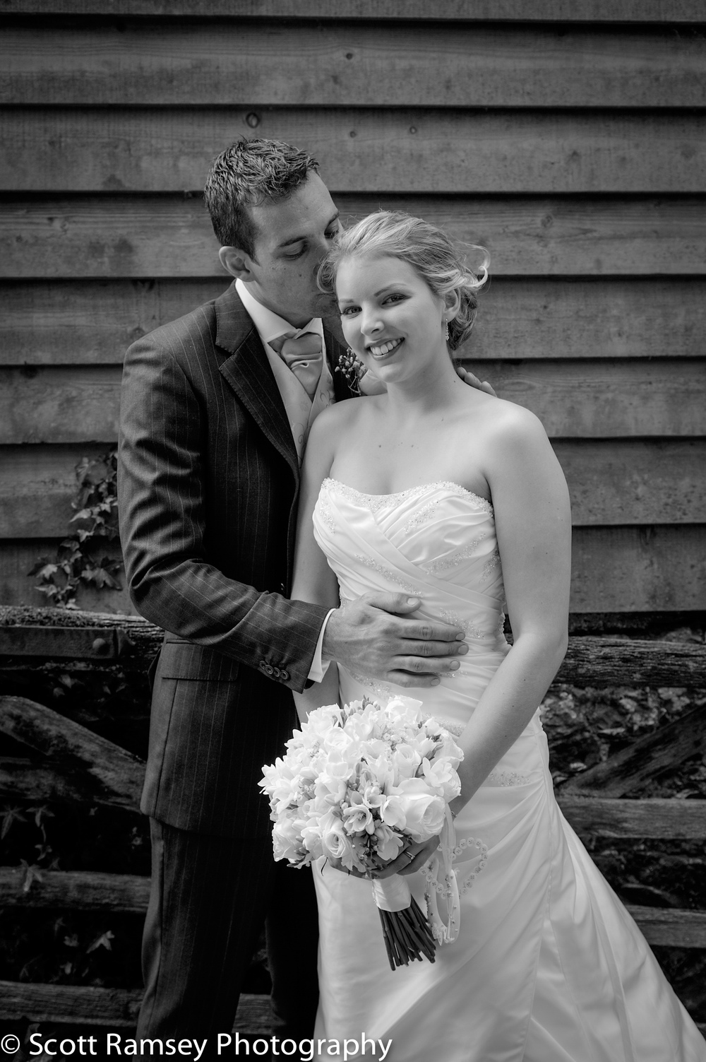 The Groom whispers into the ear of his bride in this very romantic photograph taken during a wedding at Mellow Farm Barn, Farnham in Surrey.