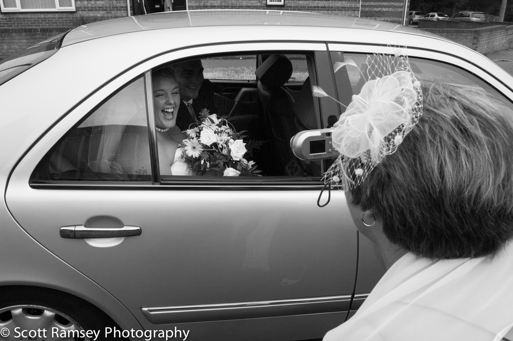 Worthing Wedding Photographer Scott Ramsey captured this fun photograph whilst photographing a wedding in Lancing, West Sussex. After the wedding ceremony the Bride and Groom are driven away from the church. As they leave the bride can be seen laughing through the car window as a wedding guest takes a photograph.