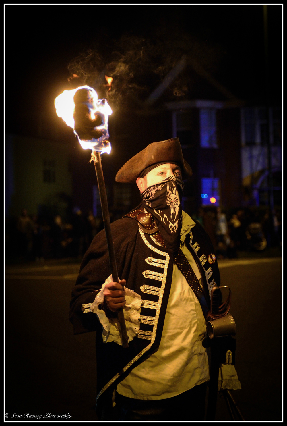 Dressed in a pirate costume and holding a flaming torch a member of the Eastbourne Bonfire Society stands in the street during the Littlehampton Bonfire Torchlight Procession.
