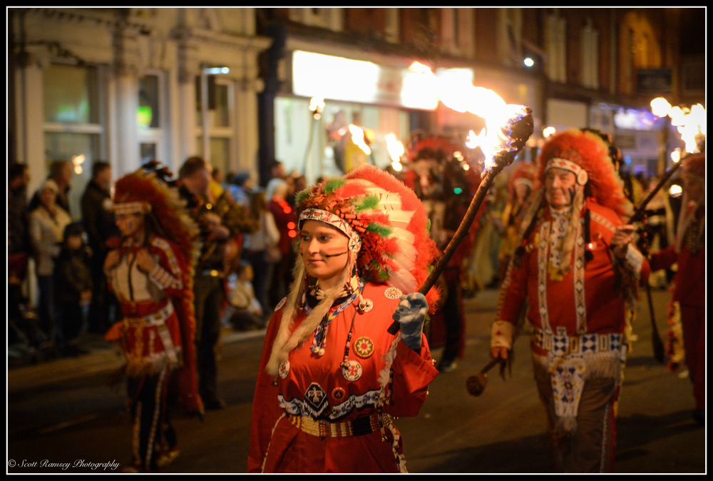 Dressed as a North American Indian a member of the Littlehampton Bonfire Society holds a flaming torch as she walks in the procession through the streets of Littlehampton.