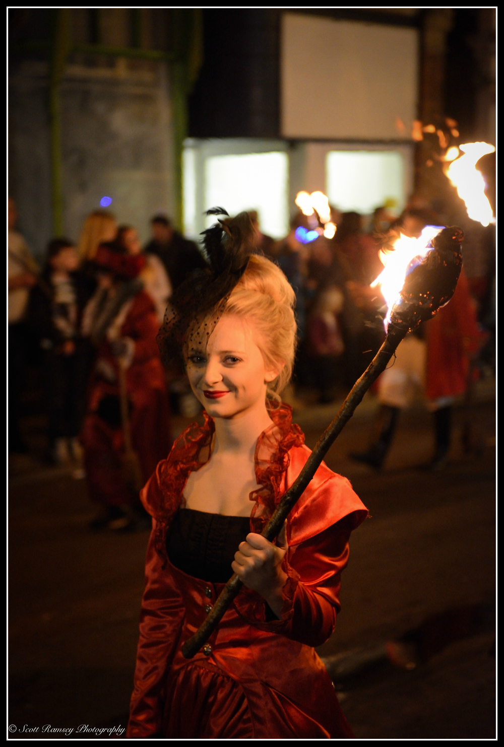 Holding a flaming torch whilst walking through the streets of Littlehampton a member of a bonfire society takes part in the torchlight procession.