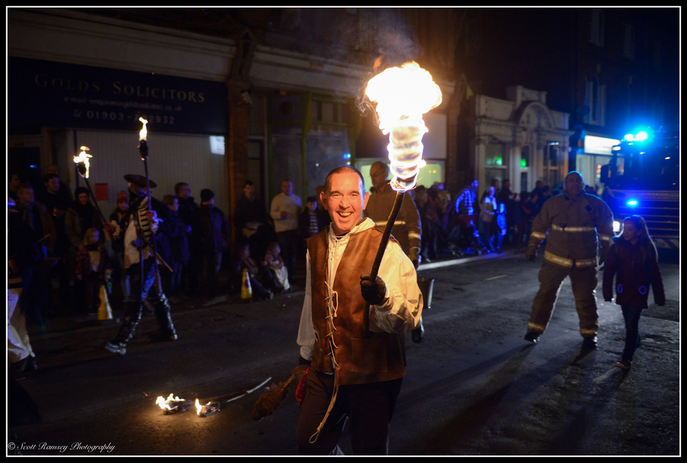 A smile for the crowd a member of the Eastbourne Bonfire Society holds a flaming torch during the Littlehampton Bonfire Night Torchlight Procession.
