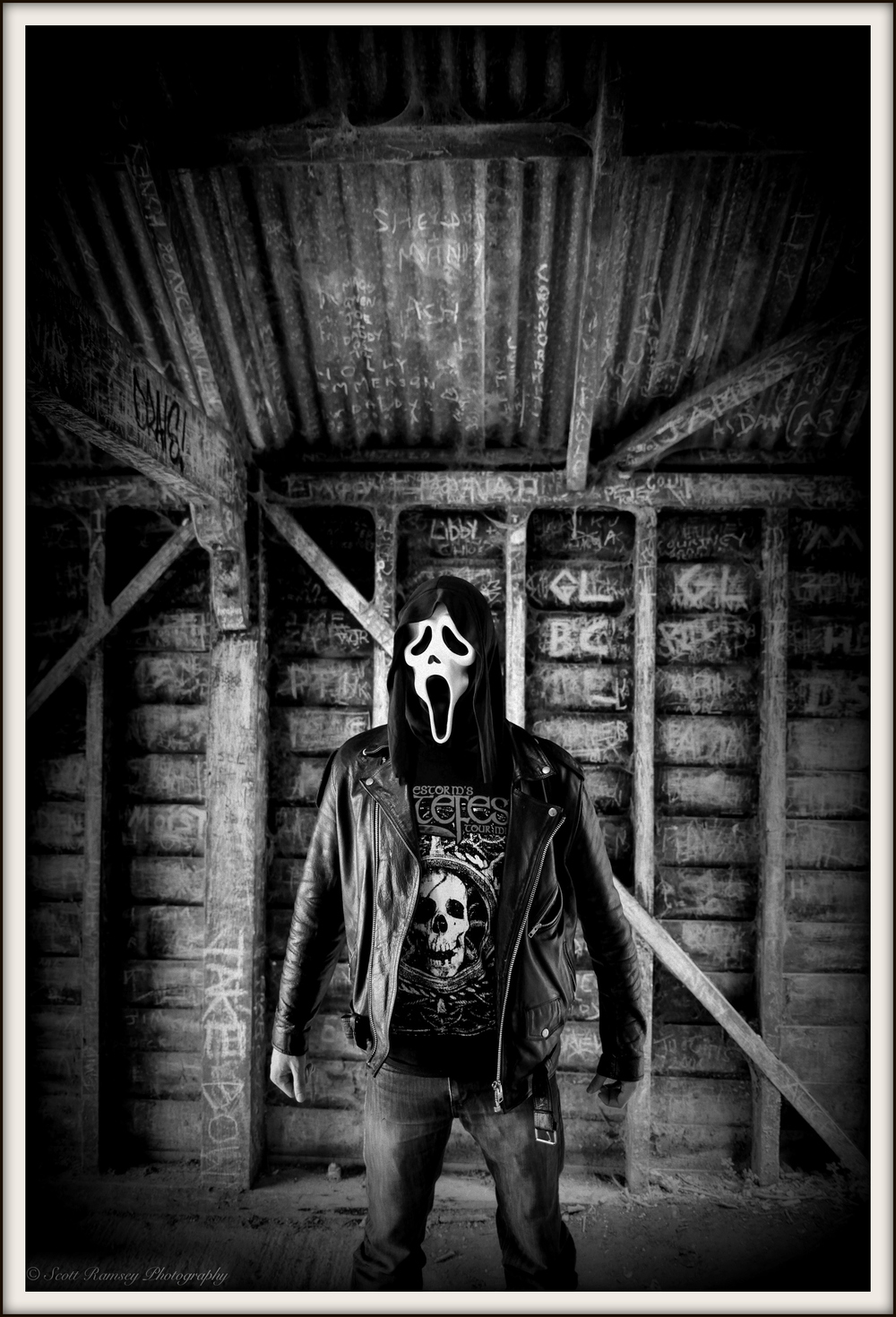 A masked man stands in front of a graffiti covered wall in this Halloween photo. © Scott Ramsey Photography