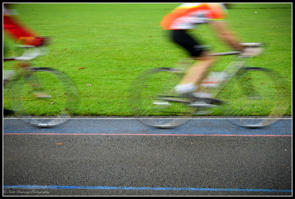 Cyclists are blurred as they speed past the camera whilst taking part in the Pedal in Preston Park charity cycle event in Preston Park Velodrome in Brighton. The track was originally dug out by hand by the British Army in 1877.