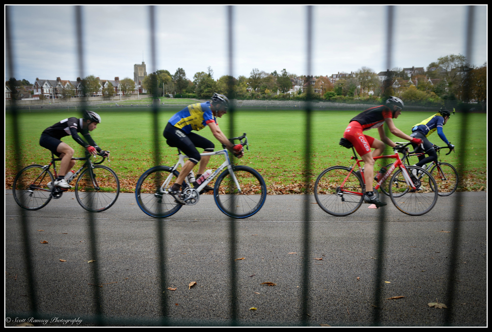 Cyclists speed past the safety fence at the Preston Park Velodrome in Brighton.