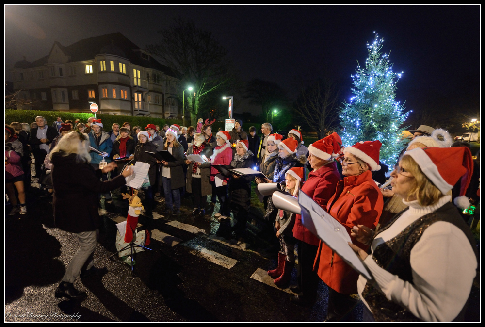 During the East Preston Christmas Celebrations, carol singers perform in front of the Christmas tree.