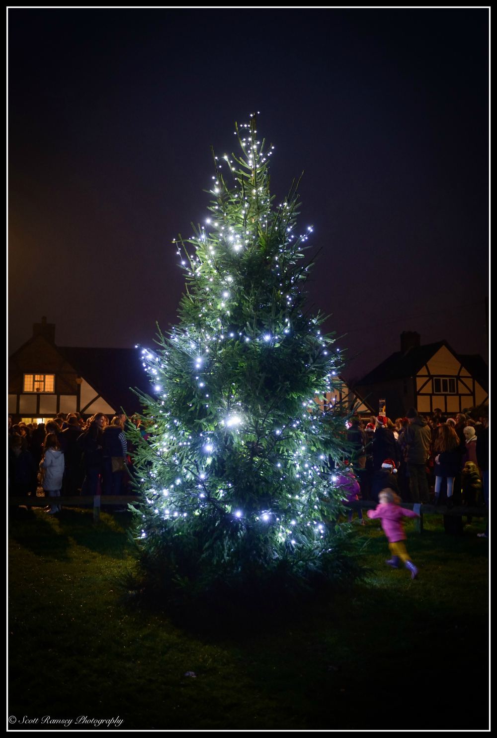 A child runs past the East Preston Christmas tree lights during the switch on event in the West Sussex village.