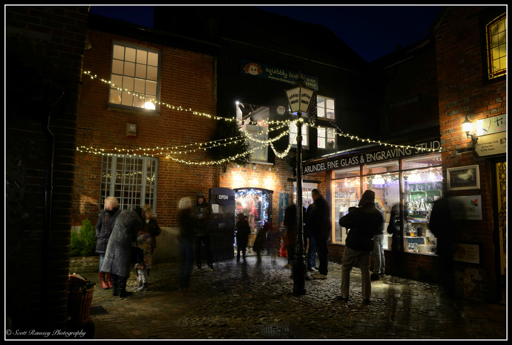 Christmas lights hang outside shops lighting the cobbled streets in Arundel West Sussex during the Arundel By Candlelight Christmas event.