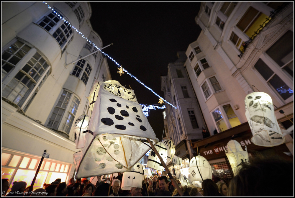 Paper lanterns are held high as the Burning The Clocks event makes its way through the streets in Brighton.