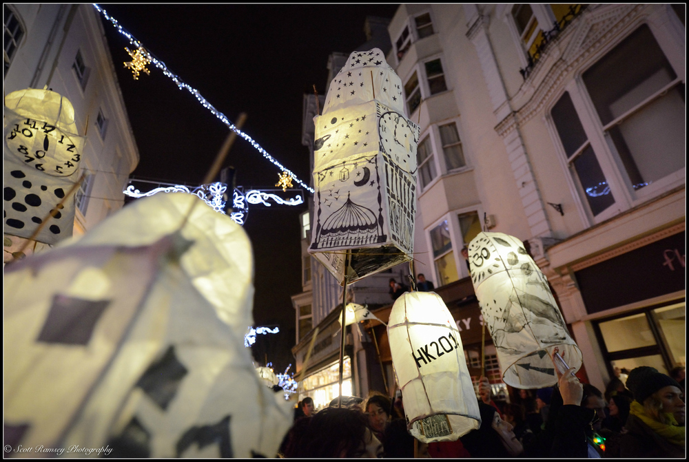 Paper lanterns, celebrating the winter solstice, are held up high lighting the dark streets in Brighton during the Burning The Clocks lantern parade in Sussex.