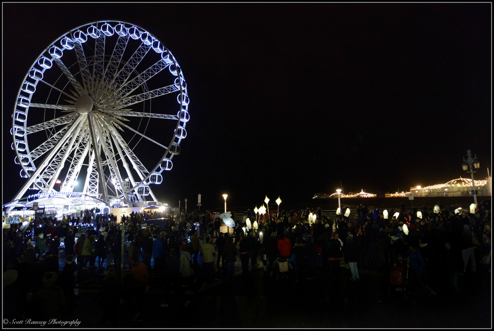 Lit paper lanterns are carried past Brighton Pier and the Brighton Wheel at night during the Burning The Clocks event in Brighton, Sussex.