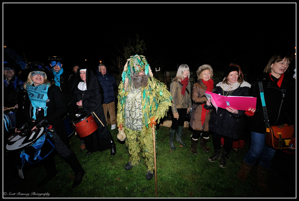 Dressed in green and holding a Wassail Cup a member of the Sompting Village Morris stands in an Apple Orchard during the annual Wassailing event at Tarring Village.