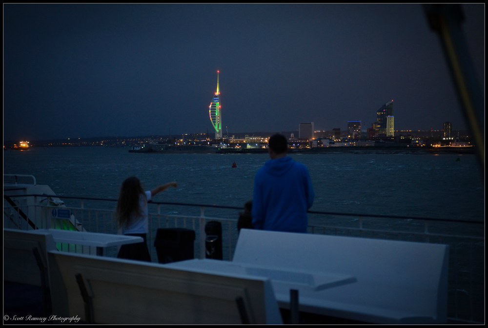 After crossing the Solent at night passengers on the Isle of Wight ferry stand on deck and enjoy the view. In the distance the lights of the Spinnaker Tower and Portsmouth and be clearly seen.