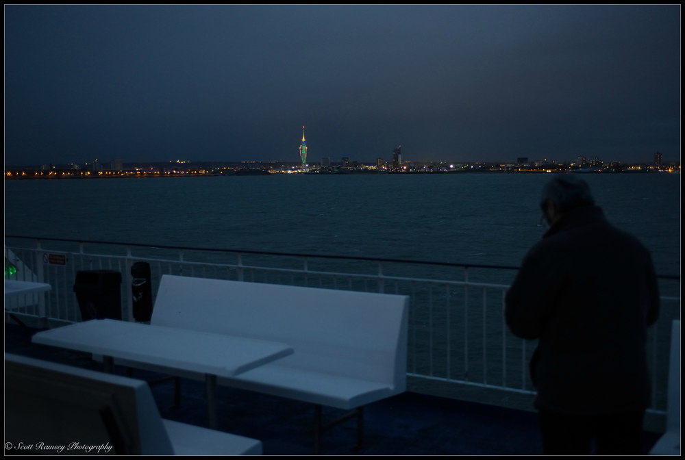 A passenger stands on deck as the night ferry nears Portsmouth.