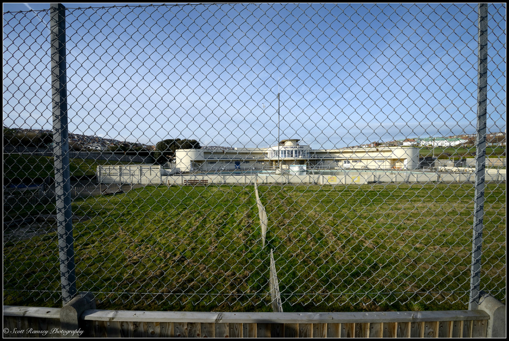 The view of Saltdean Lido in East Sussex through a fence. © Scott Ramsey Photography