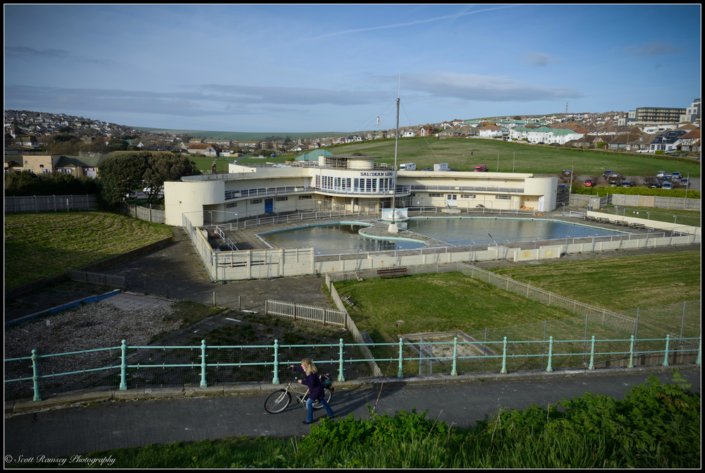 A cyclist pushes her bike up a steep walk way in front of the derelict Saltdean Lido in East Sussex, UK. © Scott Ramsey Photography