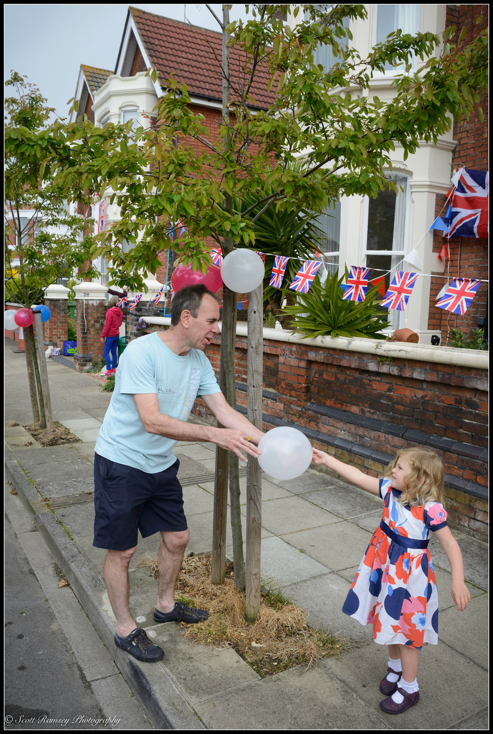 A resident of Nettlecombe Avenue, Southsea is handed a balloon from a young girl during preparations for VE Day 70th anniversary street party. © Scott Ramsey Photography.