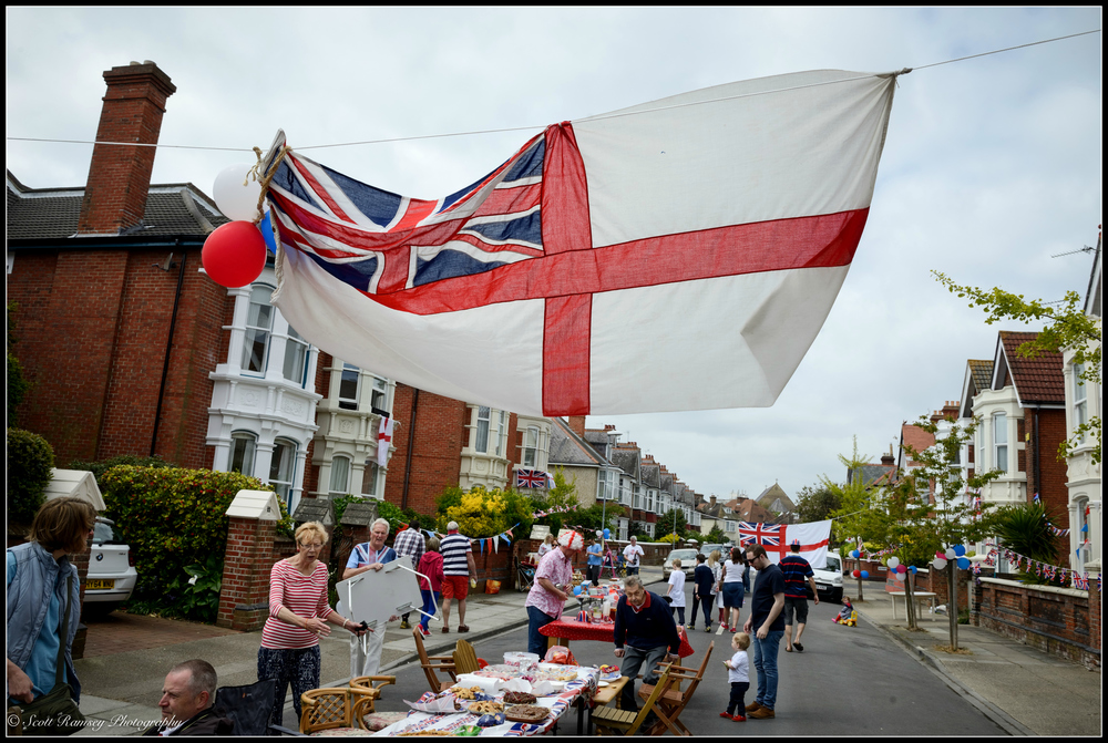 Flags flutter in the wind above the heads of residents as they prepare for the VE Day street party in  Nettlecombe Avenue in Southsea, Portsmouth   . © Scott Ramsey Photography.