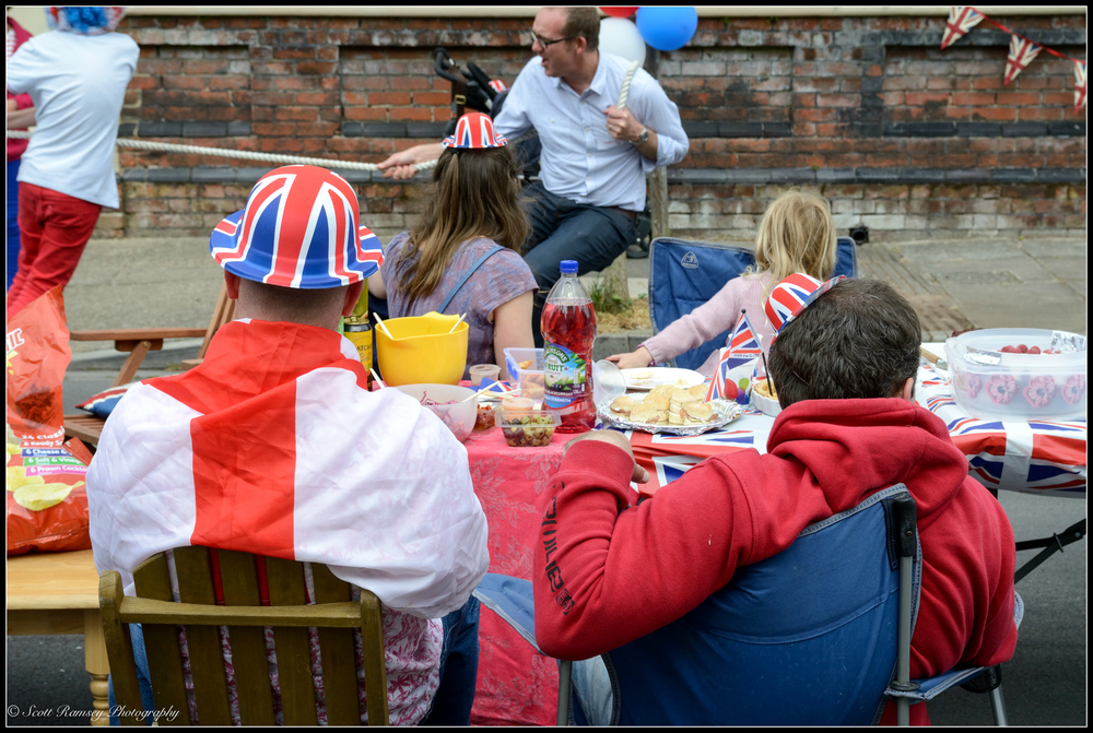 Two residents wearing union jack party hats sit in front of a table of food during a VE Day 70th anniversary street party in Southsea, Portsmouth, UK. © Scott Ramsey Photography.