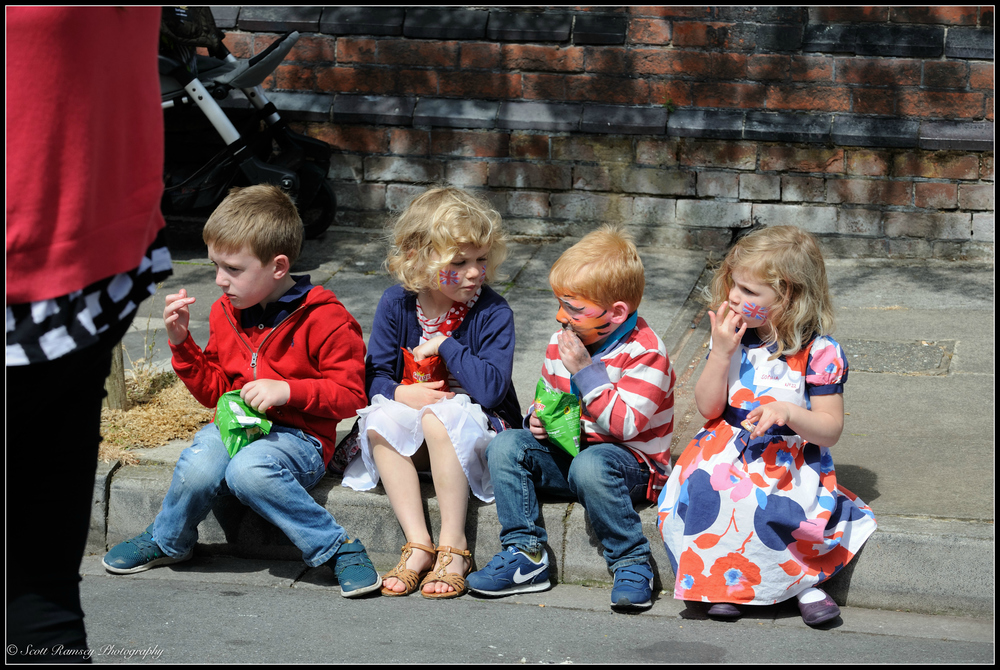 Children sit on the curb eating crisps and cakes whilst enjoying the VE Day 70th anniversary street party in Southsea, Portsmouth. © Scott Ramsey Photography.