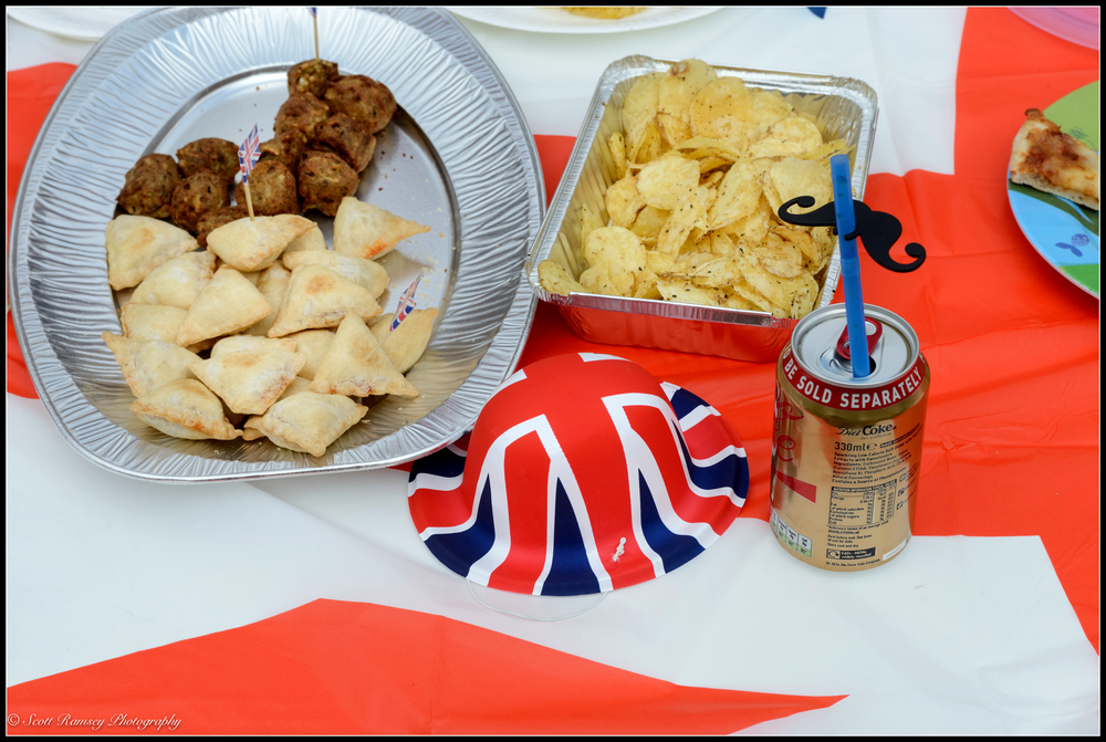 Party food, drink and a union jack party hat on a Saint Georges flag table cloth. VE day 70th anniversary street party in Southsea. © Scott Ramsey Photography.