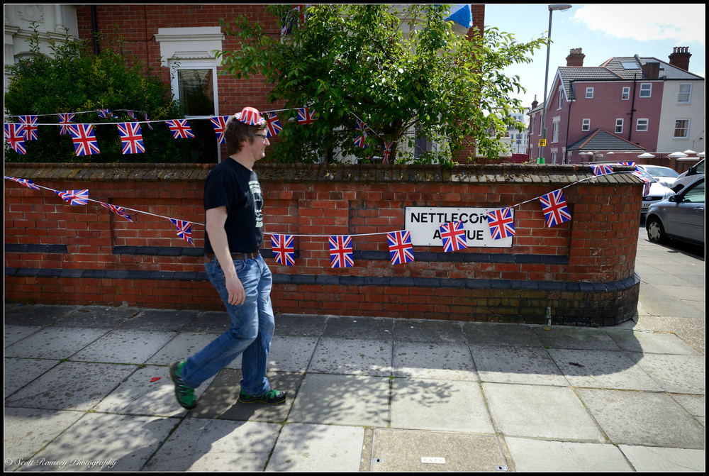 A man wearing a party hat walks past flags hung above a Nettlecombe Avenue street sign as he leaves the   VE Day 70th anniversary street party in Southsea, Portsmouth, UK.   © Scott Ramsey Photography.