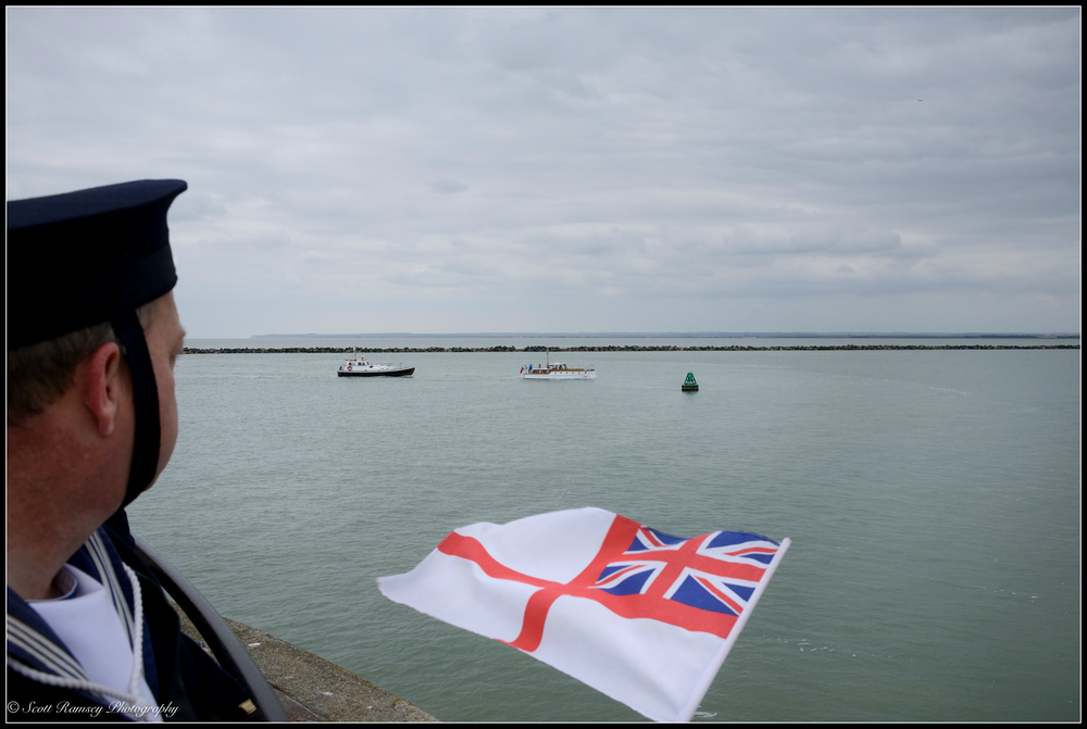 A spectator dressed in a sailors uniform holds a flag as he looks at one of the first of the Dunkirk Little Ships to return to the Royal Harbour Marina Ramsgate, Kent, UK during a weekend of events to commemorate the 75th anniversary of Operation Dynamo. ©Scott Ramsey Photography
