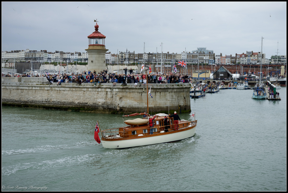 Spectators wave flags and cheer as The Hilfranor, a 1935 motor yacht and one of the original Dunkirk Little Ships, returns to the Royal Harbour Marina Ramsgate during a weekend of events to commemorate the 75th anniversary of Operation Dynamo. ©Scott Ramsey Photography