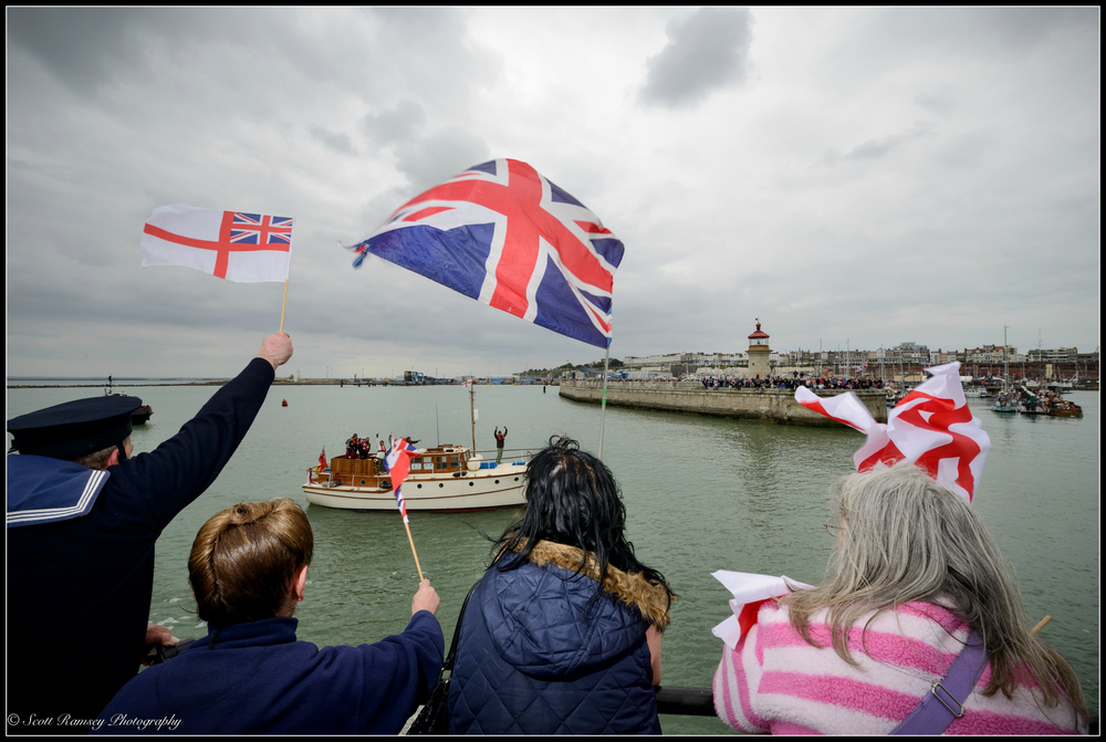 People wave flags and cheer as the Dunkirk Little Ships return to the Royal Harbour Marina Ramsgate, Kent, UK during a weekend of events to commemorate the 75th anniversary of Operation Dynamo. ©Scott Ramsey Photography