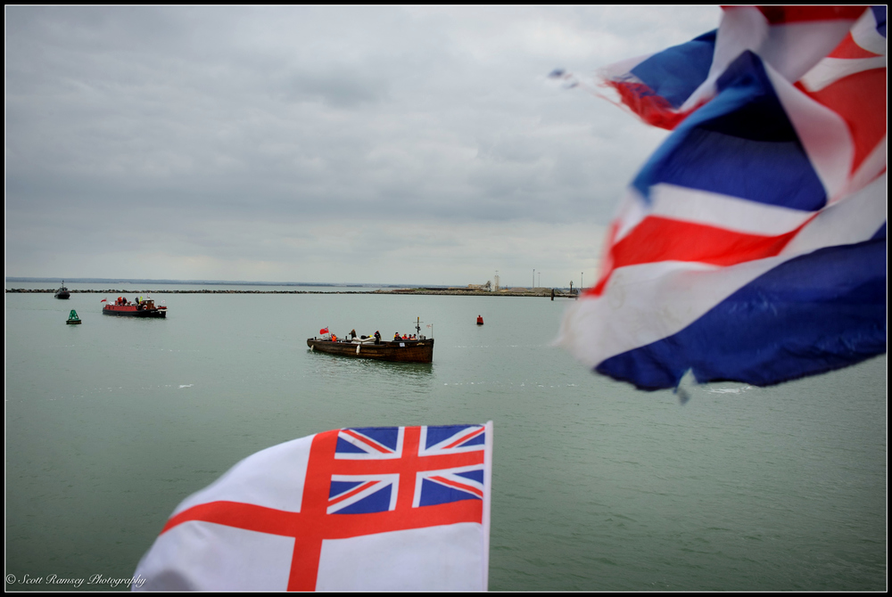 The New Britannic, a 1930 passenger boat and one of the original Bunkirk Little Ships, can be seen through the flags being wavSpectators wave flags and cheer as the Dunkirk Little Ships (centre - the New Britannic a passenger boat built in 1930) return to the Royal Harbour Marina Ramsgate during a weekend of events to commemorate the 75th anniversary of Operation Dynamo. ©Scott Ramsey Photography