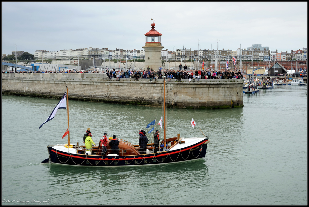 The Lucy Lavers , a 1940 RNLI lifeboat and one of the original Dunkirk Little Ships, is cheered by spectators as it returns to the Royal Harbour Marina Ramsgate in Kent, UK, during a weekend of events to commemorate the 75th anniversary of Operation Dynamo.  ©Scott Ramsey Photography