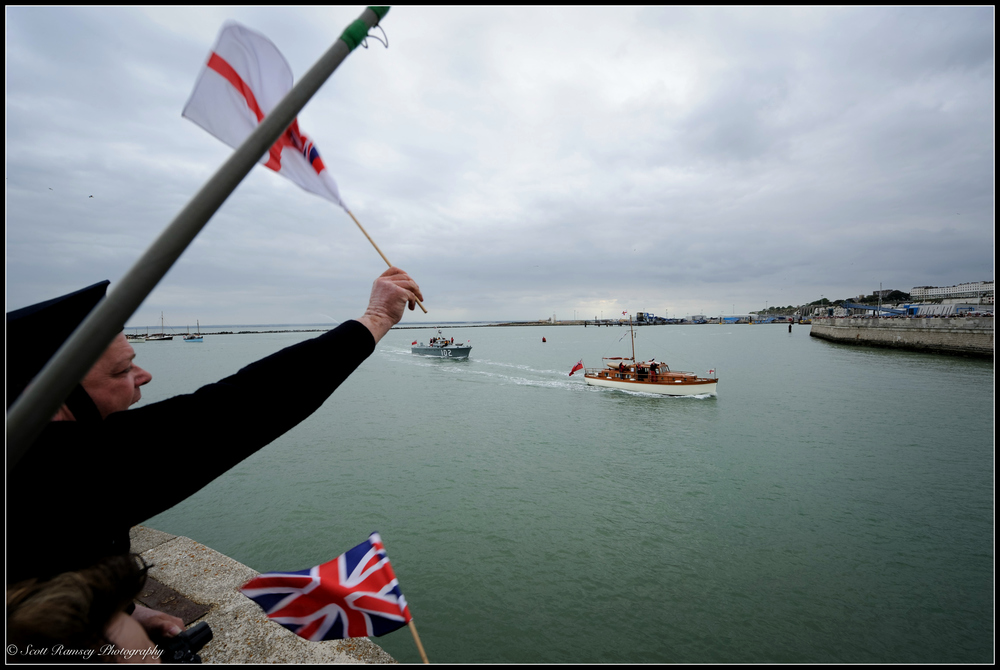 Spectators wave flags and cheer as the Dunkirk Little Ships, the 1937 Motor Torpedo Boat 102 and Hilfranor a 1935 motor yacht, return to the Royal Harbour Marina Ramsgate during a weekend of events to commemorate the 75th anniversary of Operation Dynamo. ©Scott Ramsey Photography