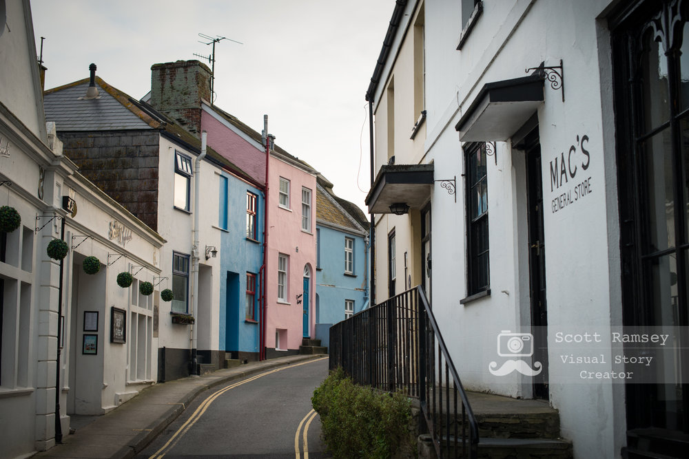 Looking past the Mac's General store in Fore St, Salcombe colourful houses can be seen further along the road. Photo © Scott Ramsey