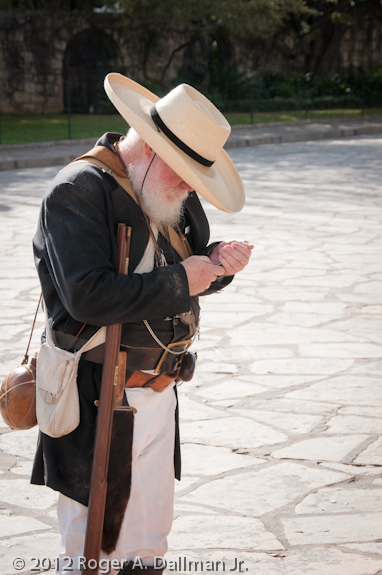 Re-enactor on cell phone at the Alamo.
