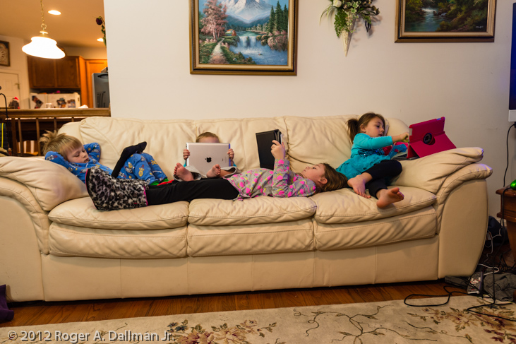 unmodified photo of children on couch with iPads
