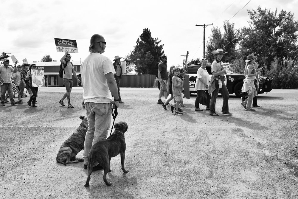 An Alpine ctizen looks on as people march in opposition to the Trans-Pecos pipeline. The Big Bend region is home to a diverse group of people, most of whom have expressed concern about the potential indutrialization of this region.