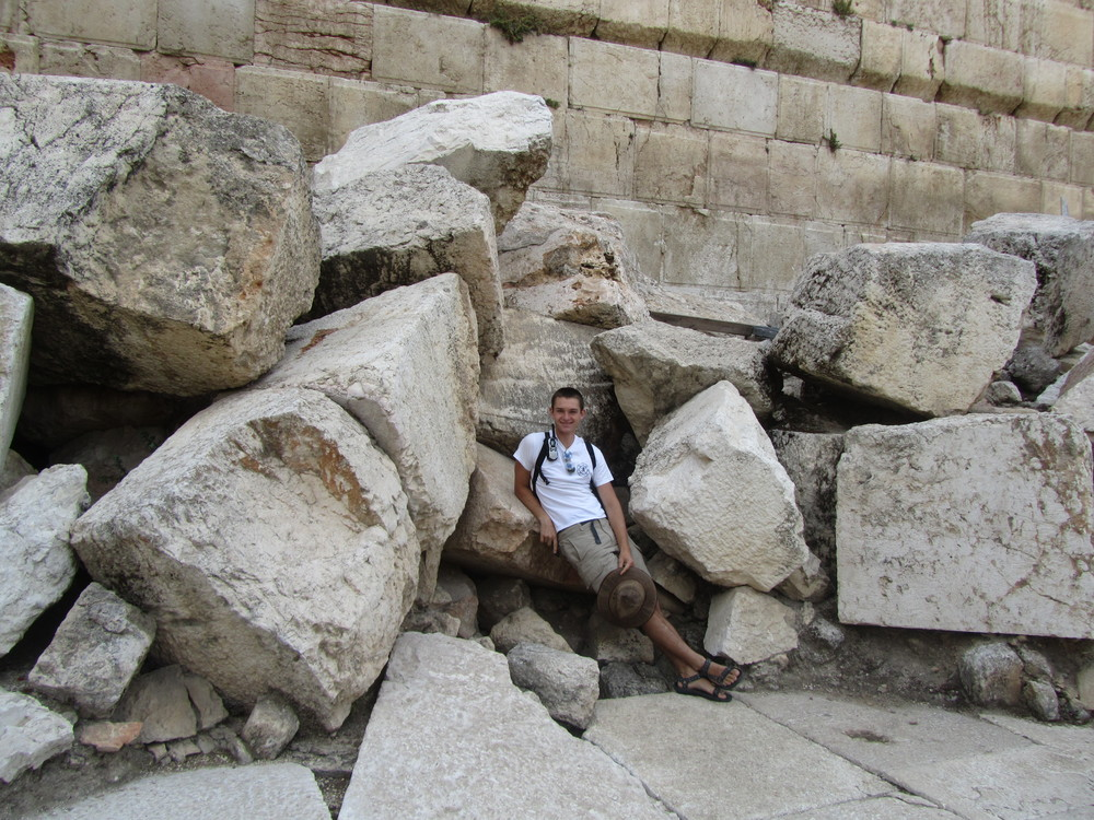Luke lounging on a small pile of the massive Temple stones thrown down by the Romans nearly 2000 years ago