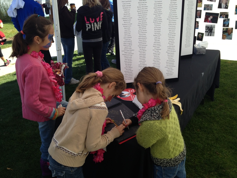 "The girls signing the memory book.  Their messages said, ""I miss you, Grammie.  I love you."""